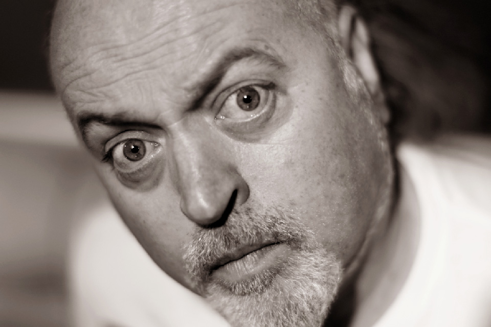 A close up black and white photograph of comedian Bill Bailey.