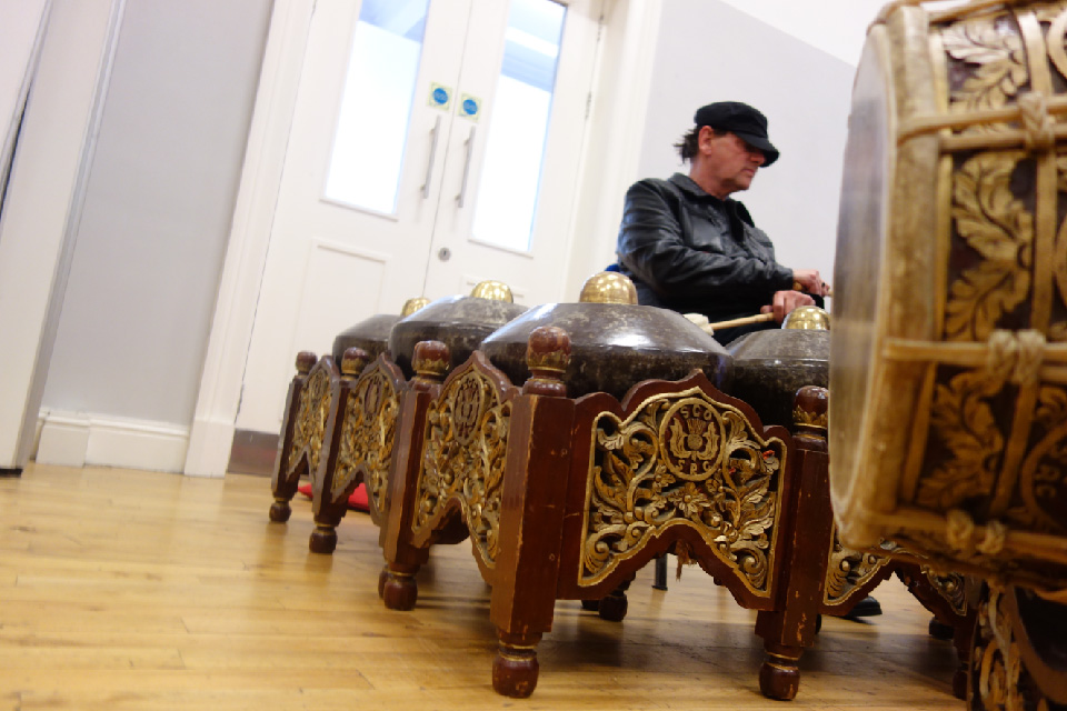 White man wearing a leather jacket and black cap with gamelan instruments.