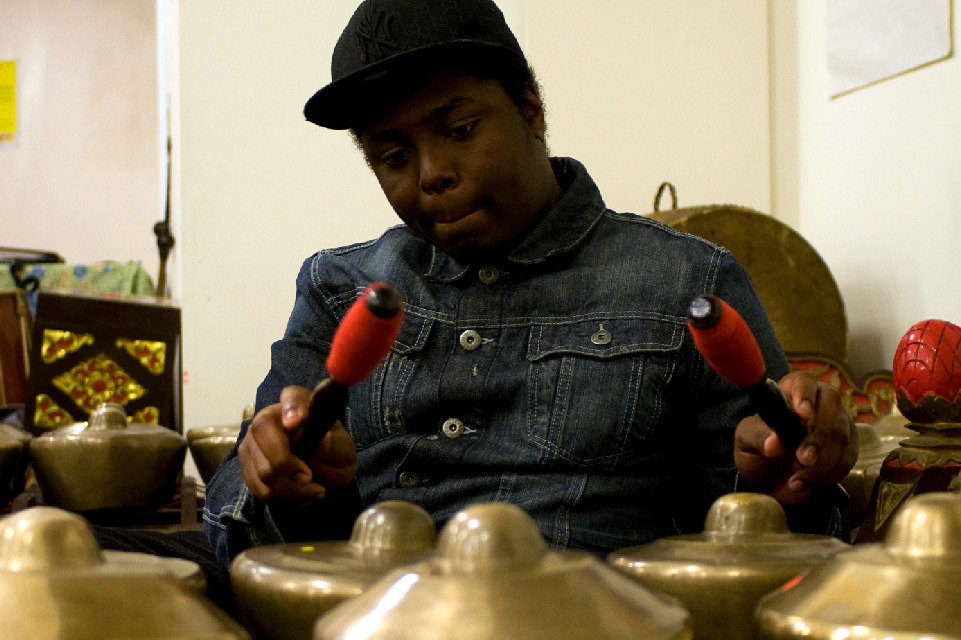 Young black man wearing a cap and looking focussed while playing gamelan.
