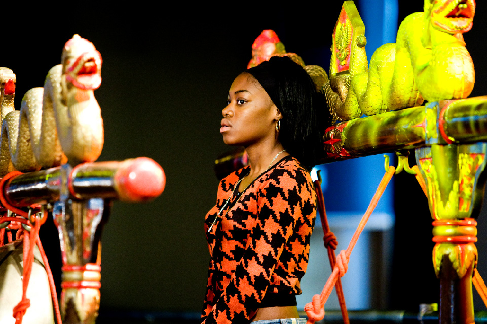 Young black woman standing up, surrounded by gamelan instruments.
