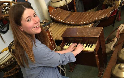 White woman smiling at the camera while playing piano.