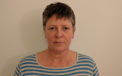 White woman with short grey hair standing against a white wall.