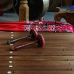 Two wooden and red beaters on a wooden xylophone, with a decorative piece of red cloth and some metal gongs in the background.