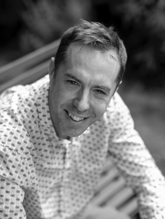 Black and white photograph of Chris Atkins, white man with short hair, wearing a white patterned shirt.