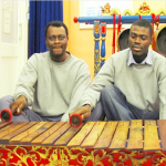 Two young black men in grey sweatshirts playing a wooden xylophone together, as part of a gamelan orchestra.