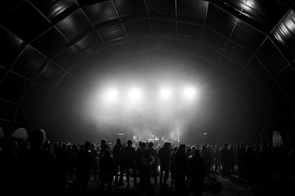 Black and white photograph of a large standing audience in a huge, spacious venue that looks like a warehouse.
